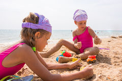Two children playing in sand on the beach resort. Two children playing in the sand on the beach resort Royalty Free Stock Image