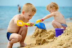 Two children playing with sand at ocean beach Stock Photo