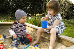 Two Children Playing In A Sandbox. One year old boy and three year old girl playing in a sandboox Royalty Free Stock Photos
