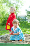 Two children playing in sandbox. Two children playing with sand in sandbox Royalty Free Stock Photo