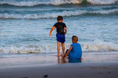 Two Children playing on sandy beach near sea stock image