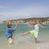 Two children playing in the sea Stock Photography