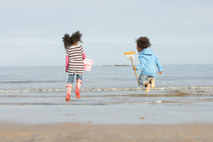 Two Children Playing By Sea On Winter Beach Royalty Free Stock Images
