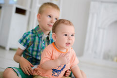 Two children are playing while sitting on the floor at home.  Royalty Free Stock Photos