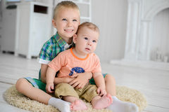 Two children are playing while sitting on the floor at home.  Royalty Free Stock Images