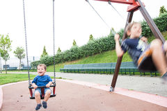 Two children playing in the swing Royalty Free Stock Photography
