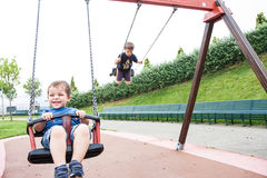 Two children playing in the swing Royalty Free Stock Image