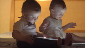 Two children playing with a tablet stock footage