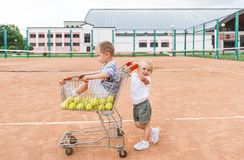 Two children playing on tennis court. Little boy and tennis balls in the shopping cart. royalty free stock photos