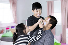 Two children playing with their father Stock Photos