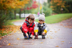 Two children, playing with toys in the park on a rainy day Royalty Free Stock Photo