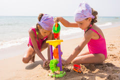Two children playing with toys in the sand on the sea beach Stock Images