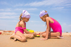 Two children playing with toys in sand on the sea beach Royalty Free Stock Photos