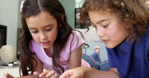 Two children are playing video games. In the lounge stock footage