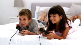 Two children playing video games. Lying on a bed stock video footage
