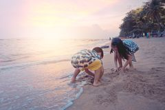 Two children is playing with wave and sand in Pattaya Beach Thailand stock photo