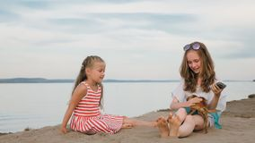 Two children playing which dogs on the sand on the beach. Kid play with dogs. They squeeze them, throw them up. The girls are wearing sunglasses. Dogs Toy Stock Photo