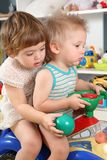Two children in playroom on toy scooter Royalty Free Stock Photography