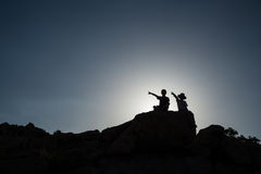 Two children pointing, sitting on rock. Boy and girl on top of rock pointing royalty free stock photos