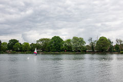 Two children practice sailing on a Spring day in South Norwood l Royalty Free Stock Images