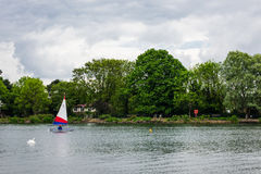 Two children practice sailing on a Spring day in South Norwood l Royalty Free Stock Photography