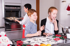 Two children preparing christmas bakery - mother puts cookies in Royalty Free Stock Image