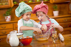 Two children preparing eggs for cookies in the kitchen Royalty Free Stock Images