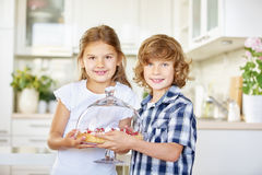 Two children presenting a cake Stock Images