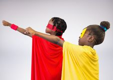 Two children pretending to be a superhero. Standing against white background Stock Photos