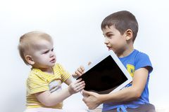 Two children quarrel, because of the tablet PC, children`s conflict royalty free stock images