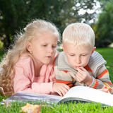 Two children read the book on a lawn Royalty Free Stock Photos