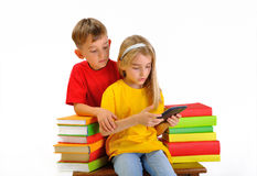 Two children read e-book surrounded by books
