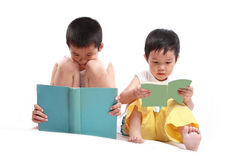 Two children reading book. The two chinese children sat on the floor reading book with white background Royalty Free Stock Image