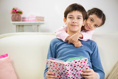 Two children reading book at home Stock Photos