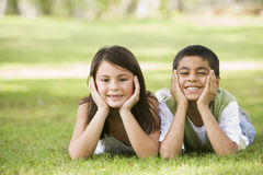 Two children relaxing in park Royalty Free Stock Image