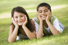 Two children relaxing in park Stock Images