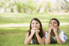 Two children relaxing in park Royalty Free Stock Photography