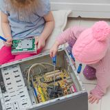 Two children repair a computer, a system unit. Girls, two children repair the computer system unit with a screwdriver Royalty Free Stock Photography