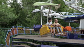 Two children ride on the carousel in an amusement park stock video