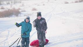 Two children ride on a snowy hill on a sled. Children climb to the top of the mountain. Walks in the fresh air. Two children ride on a snowy hill on a sled stock video footage