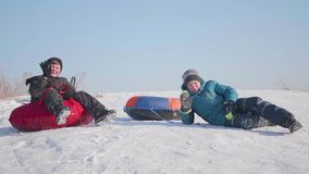Two children ride on a snowy hill on a sled. Children sit on top of the mountain. Sport and outdoor activities. Two children ride on a snowy hill on a sled stock video