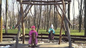 Two children riding on a horse swings. Two little girls in the late autumn ride on wooden chain swing - horses stock video footage