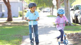 Two Children Riding Scooters Towards Camera. Children riding scooters into focus as they approach camera. Shot on Canon 5d Mk2 with a frame rate of 30fps stock video footage
