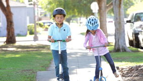Two Children Riding Scooters Towards Camera. Children riding scooters into focus as they approach camera. Shot on Canon 5d Mk2 with a frame rate of 30fps stock footage