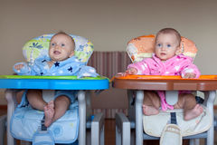 Two children in robes in high chair indoor Stock Image