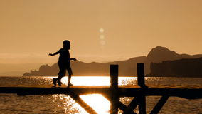 Two Children Running On Bridge At Sunset. Picturesque footage of beautiful sunset on the beach and silhouette of two children running on the bridge stock footage