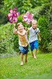 Two children running in garden in summer Royalty Free Stock Images