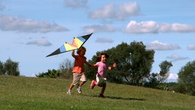 Two children running with kite in park. Together stock video footage