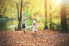 Two children running near the autumn pond Royalty Free Stock Images