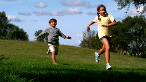 Two children running in park Stock Image
